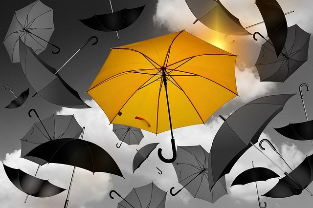 Yellow umbrella among black umbrellas